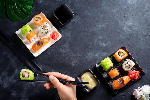 Verschillende verse en heerlijke sushi op witte leisteen, hand met leisteen stokken