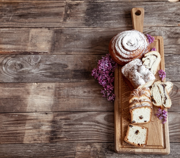Verschillende verse gebakjes worden gesneden op een houten stok, versierd met bovenaanzicht van lila bloemen.