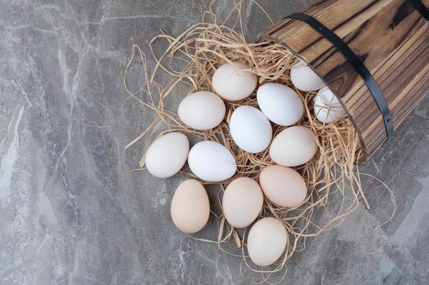 Verschillende verse kippeneieren op hooi op marmeren achtergrond. hoge kwaliteit foto