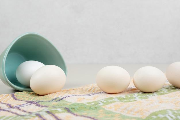 Verschillende verse witte kippeneieren in blauw bord op tafellaken.