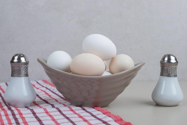 Verschillende verse witte kippeneieren in grijze plaat op tafellaken.