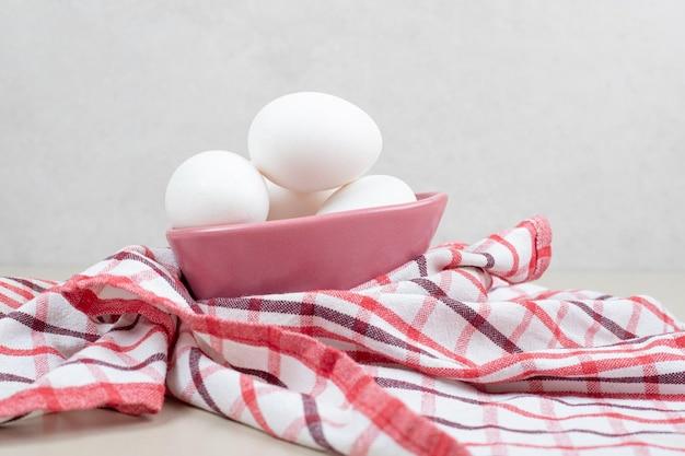 Verschillende verse witte kippeneieren in roze plaat op tafellaken.