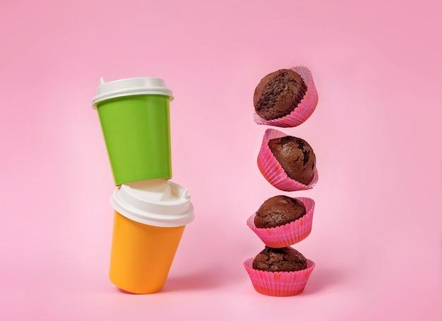 Verschillende vliegende cupcakes en twee glazen voor koffie en thee op roze