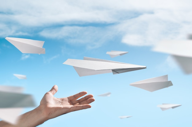 Verschillende vliegende papieren vliegtuigen. mannenhand in het frame.