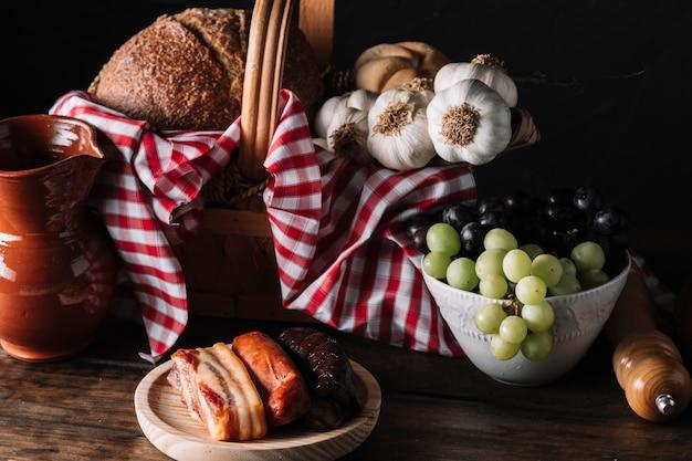 Verschillende voedsel en kruik in de buurt van de mand