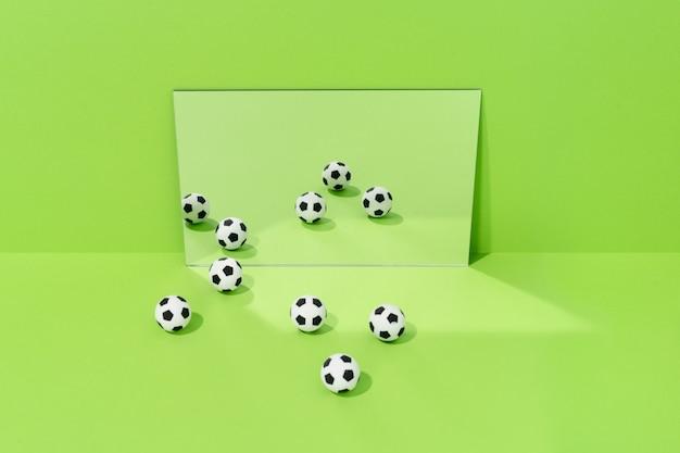 Verschillende voetballen weerspiegeld in een spiegel op een groene achtergrond. concept van voetbal en sport.