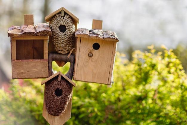 Verschillende vogelhuisjes en een vogelvoeder op een stokje.