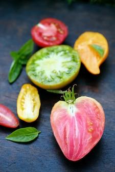 Verschillende vormen en kleuren tomaten op een donkere achtergrond