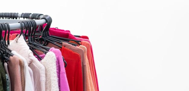 Verschillende vrouwelijke kleren op kleerhangers.