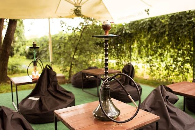 Verschillende waterpijpen in de natuur op een warme zonnige dag. oosterse waterpijp roken, actieve recreatie in de frisse lucht. ligstoelen op geen gras. de plek voor vrije tijd,