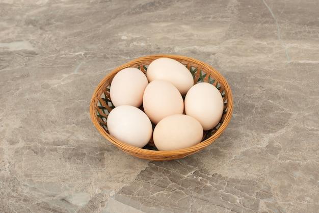 Verschillende witte eieren in een rieten mand