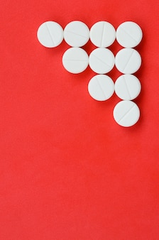 Verschillende witte tabletten liggen op een felrode achtergrond in de vorm van een driehoekige pijl