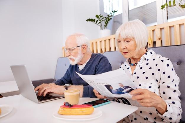 Verschillende zaken. zelfverzekerde senior man met behulp van laptop en senior vrouw krant studeren