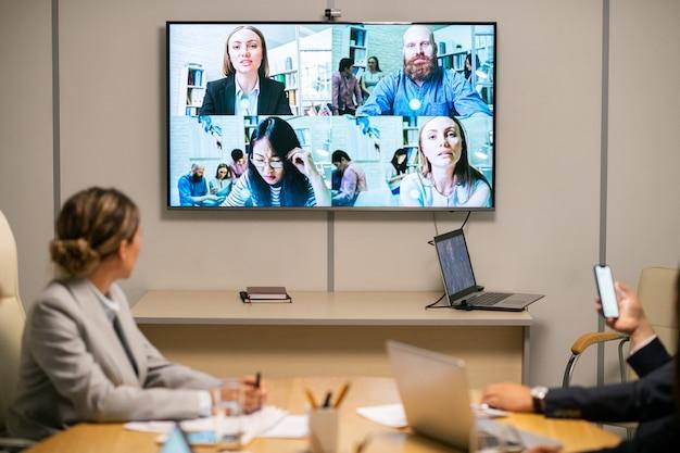 Verschillende zakenmensen op groot scherm hangend aan de muur van de bestuurskamer