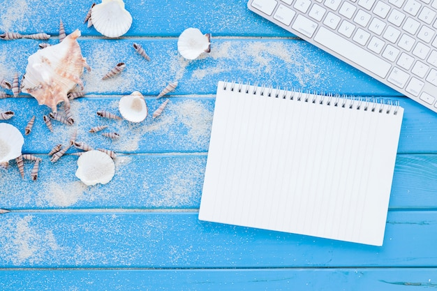 Verschillende zeeshells met notitieboekje en toetsenbord