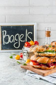 Verschillende zelfgemaakte bagelsandwiches met sesam- en maanzaad, roomkaas, ham, radijs, rucola, cherrytomaatjes, komkommers, wit grijs getextureerd oppervlak