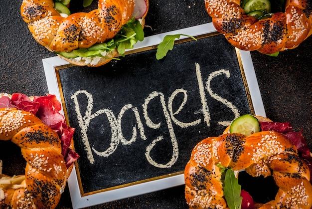 Verschillende zelfgemaakte bagelsandwiches met sesam- en maanzaad, roomkaas, ham, radijs, rucola, kerstomaatjes, komkommers, donker betonnen oppervlak hierboven
