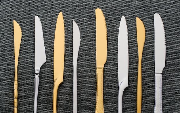 Verschillende zilveren en gouden messen op een zwart servet