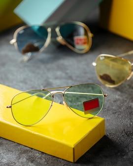 Verschillende zonnebrillen ontworpen rond lege verpakkingen op het grijze oppervlak