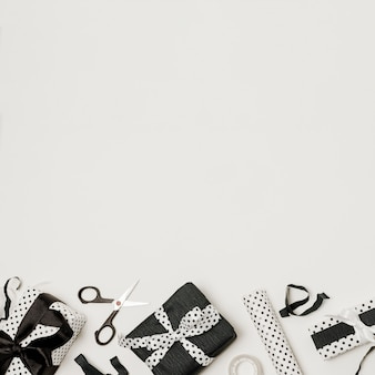 Verschillende zwart-wit verpakte geschenkdozen met schaar en designpapier