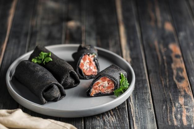 Verschillende zwarte inktvis inkt pannenkoeken met zalm en kaas vullen op een grijze plaat