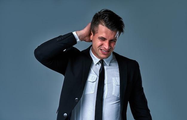 Verschrikkelijke hoofdpijn. jonge man in zwart-wit pak die zijn hoofd aanraakt en zijn ogen gesloten houdt terwijl hij tegen een grijze achtergrond staat.