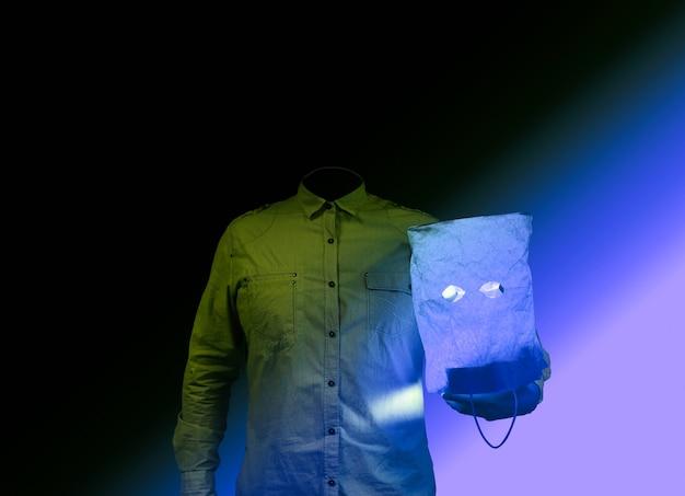 Verschrikkingsconcept. man zonder hoofd houdt een papieren zak vast. halloween-ideeën. griezelige sfeer. overhemd in plaats van persoon. zwarte achtergrond.