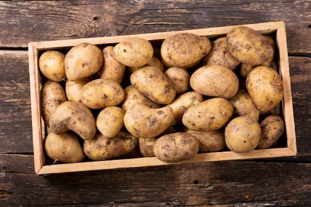 Verse aardappelen in houten kist op houten tafel, bovenaanzicht