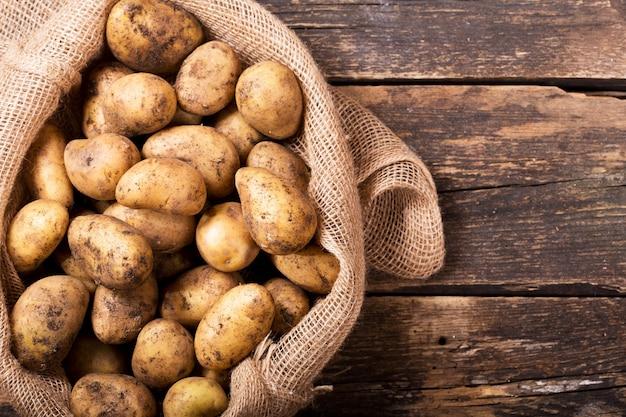 Verse aardappelen in zak op houten tafel, bovenaanzicht