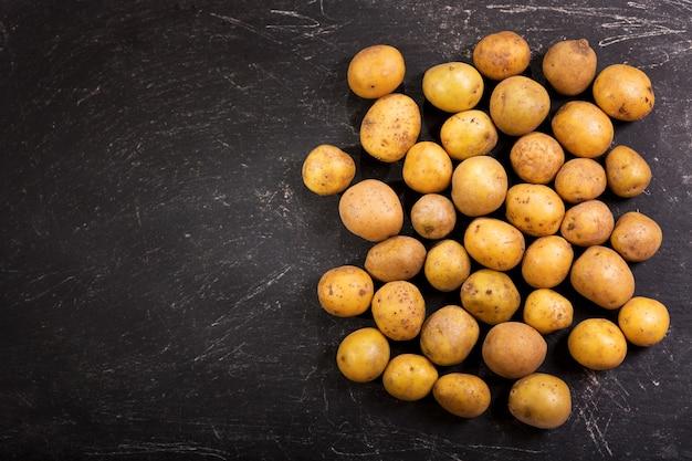 Verse aardappelen op donkere tafel, bovenaanzicht met kopie ruimte