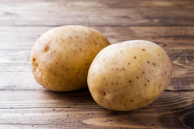 Verse aardappelen op houten tafel.