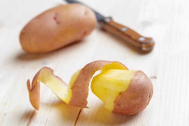 Verse aardappels op de houten achtergrond