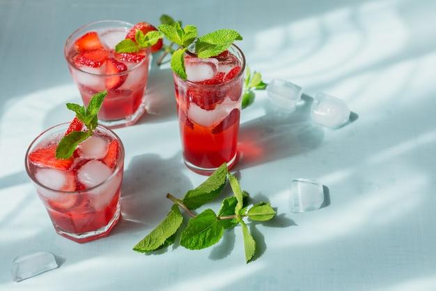 Verse aardbeicocktail. zomer roze cocktail met aardbei, groene muntblaadjes en ijsblokjes op lichtblauw