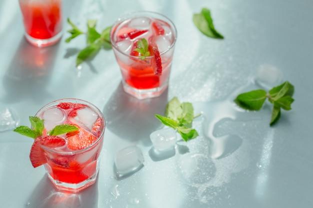 Verse aardbeicocktail. zomer roze cocktail met aardbei, groene muntblaadjes en ijsblokjes op lichte blu