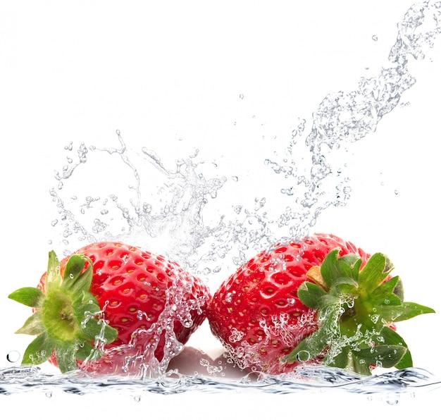 Verse aardbeien die in water vallen
