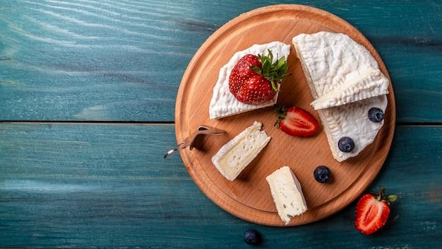 Verse aardbeien en brie kaas op een houten bord