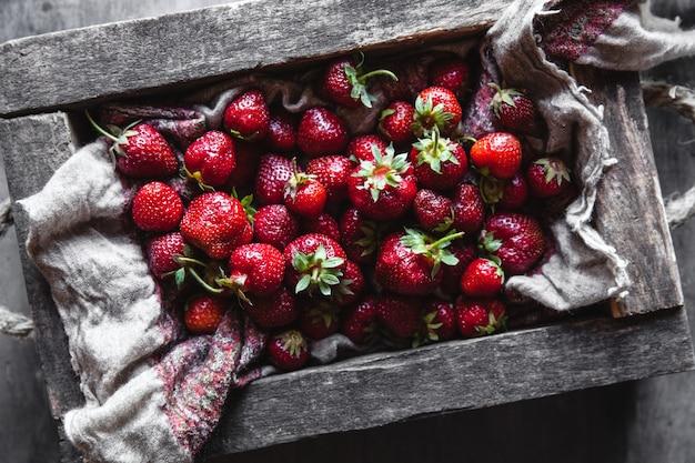 Verse aardbeien in de doos op houten vintage tafel, gezonde voeding, fruit