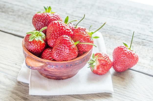 Verse aardbeien in de kom op de houten tafel