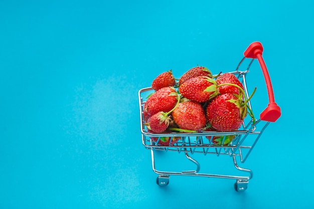 Verse aardbeien in een boodschappenwagentje op een blauwe achtergrond.