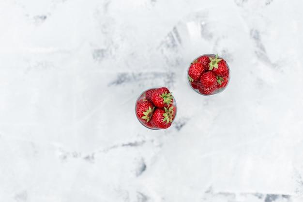 Verse aardbeien in een glas op een witte achtergrond, bovenaanzicht
