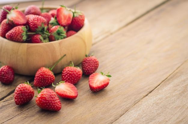 Verse aardbeien in een kom op houten achtergrond.