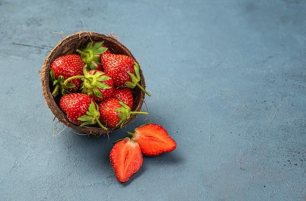 Verse aardbeien in een kopje en kokosnoot op een donkere achtergrond. zijaanzicht, kopieer ruimte.