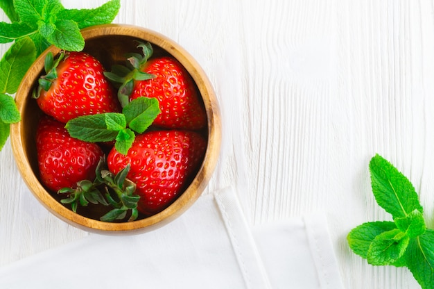 Verse aardbeien in houten kom en muntblaadjes op witte houten achtergrond.