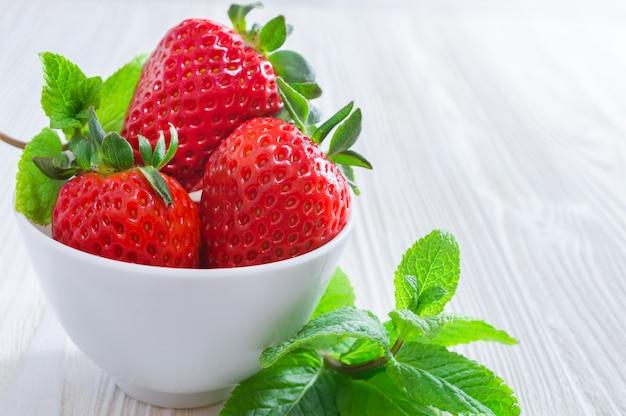 Verse aardbeien in witte kom en muntblaadjes op witte houten achtergrond.
