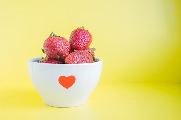 Verse aardbeien in witte kom met rood hart op de heldere gele achtergrond met copyspace
