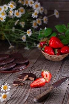 Verse aardbeien op een houten tafel met een mes, chocoladeschilferkoekjes en kamille zomerbloemen. zomer foto