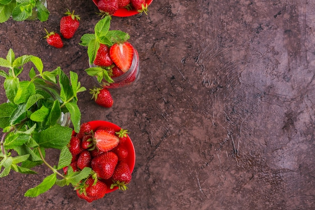 Verse aardbeien op glazen pot bovenaanzicht. gezond eten op donkere tafel mock-up. heerlijke, zoete, sappige en rijpe bes met kopie ruimte voor tekst.