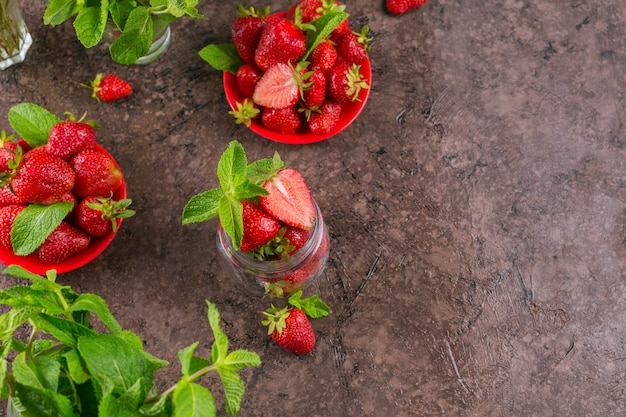 Verse aardbeien op glazen pot bovenaanzicht. gezond eten op donkere tafel mockup