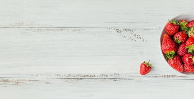 Verse aardbeien op keramische kom bovenaanzicht. gezond eten op witte houten tafel