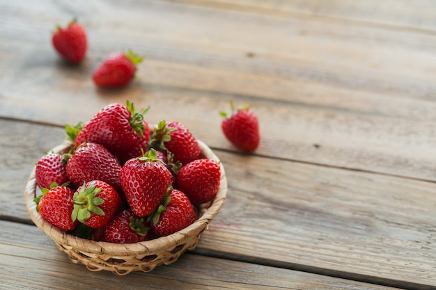 Verse aardbeien op mand bovenaanzicht. gezond eten op houten tafelmodel